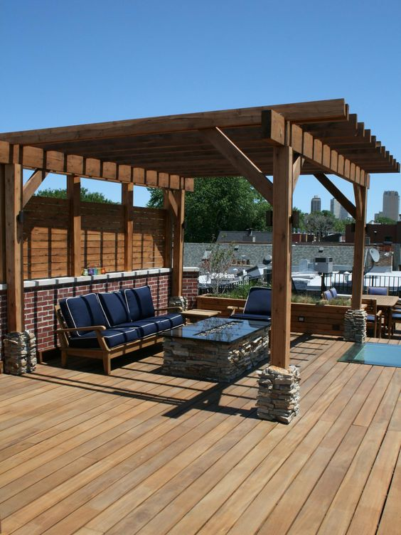 The contemporary cedar pergola provides some shade in the summer while the linear fire pit will provide for warmth in the winter, making this rooftop oasis functional year-round.