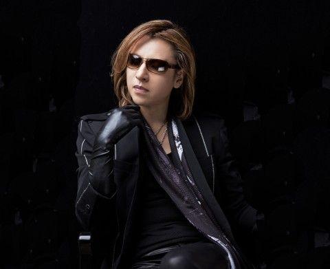 黒い衣装に黒い手袋をつけて肘をついているXJAPAN・YOSHIKIの画像