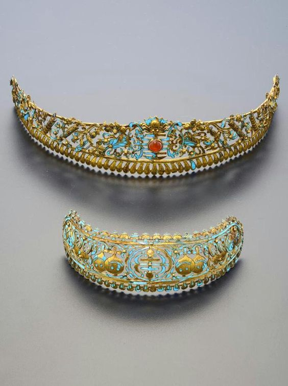 China | Two gilt metal and kingfisher feather hair ornaments; one with a central shou character set with an orange cabochon, surmounted by a bat and surrounded by auspicious objects, ribbons and foliate designs, the other with pomegranates, peaches and scrolling designs within bands of petals | Qing Dynasty | 1'200£ ~ sold (May '15)