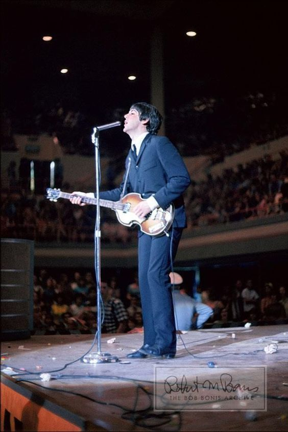 """A serene crooning Paul McCartney is juxtaposed with a beyond-littered stage in this photo taken during an August 19, 1965, show at the Sam Houston Coliseum in Houston, Texas. The Beatles played two sold-out shows in Houston, advertised as the """"Sixth Annual Back-to-School Show,"""" to capacity crowds of 9,200 screaming fans with general admission seating."""