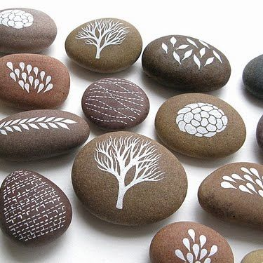 White painted stones by Natasha Newton - These would make a nifty place card. Just hand your guests a business card with a matching design on it. Then they get to match the card to the rock at their place. They could then take the rock home as a keepsake.