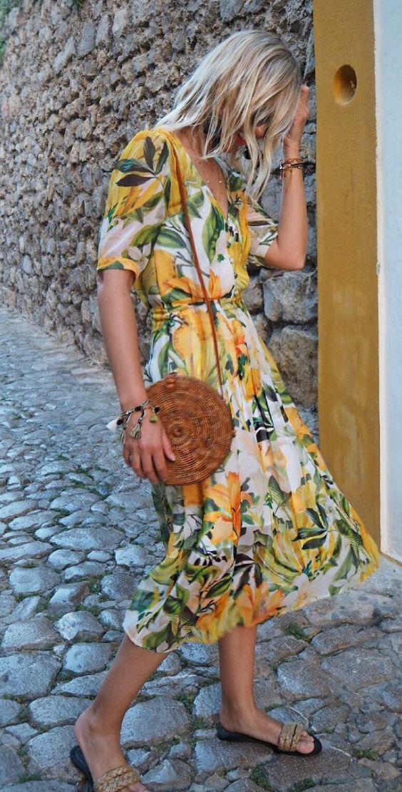 6 ideias de vestidos para você começar a pensar na primavera. Vestido bom estampa floral e folhagem amarelo, bolsa de palha redonda, sandália flat