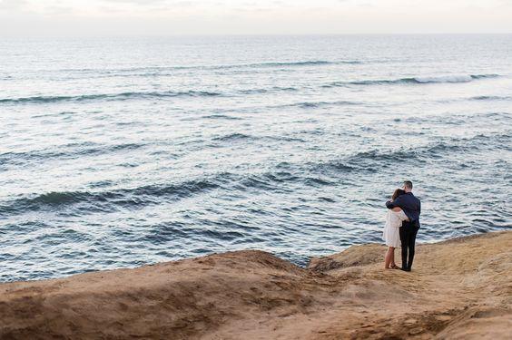man woman beach cliffside