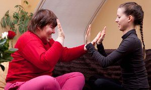 A woman and her care worker do rhythm exercises.