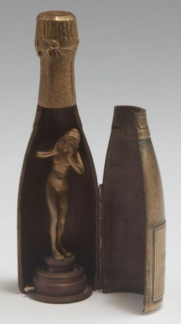 Wiener Bronze. 'Kupferberg Gold' bottle with signet, c1920. Mechanical erotic bronze. H. 12.5 cm. Nude female figure as signet inside. Marked: KUPFERBERG GOLD, Chr. Adt. Kupferberg. Mainz. GEGRÜNDET 1850.