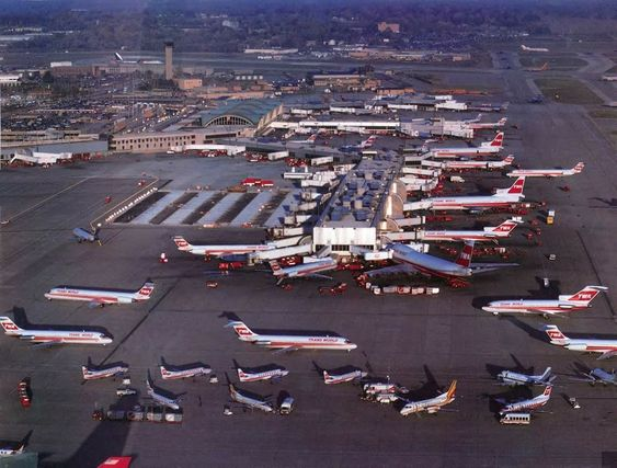 A busy day for TWA (Trans World Airlines) at the airlines' largest hub, Lambert Field (St. Louis Lambert International Airport), ca. 1985.  TWA's hub grew in 1986 when the airline bought Ozark Airlines, which operated its hub from Lambert's B, C, and D concourses. In 1985, TWA had accounted for 56.6% of boardings at STL while Ozark accounted for 26.3%, so the merged carriers controlled over 80% of the traffic.