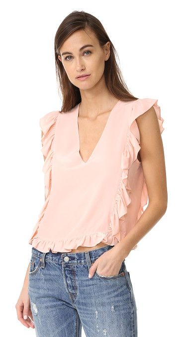 frill v neck top by Anine Bing. Charming ruffles trace the edges of this feminine ANINE BING top. Banded V neckline. Sleeveless. Fabric: Silk crepe. ...