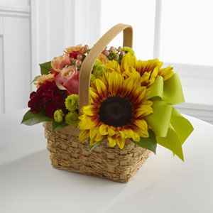 The FTD® Bright Day™ Basket is an abundant expression of Summer's beauty. Sunflowers, bi-colored pink roses, orange spray roses, burgundy miniature carnations, red hypericum berries and green button poms create a splash of sun-filled cheer when presented in a natural basket tied with a bright green ribbon, making this a lovely way to delight and dazzle your special recipient.