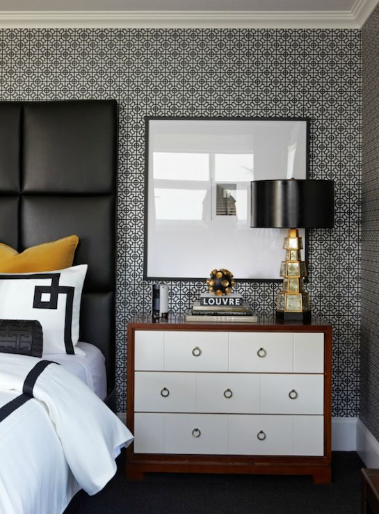 Contemporary yellow & black bedroom design white & black small geometric pattern wallpaper, yellow velvet pillows really pop against tall black leather padded headboard, white hotel duvet shams bedding with black Greek key trim, black leather Greek key bolster pillow, gold mirrored lamp with black vinyl lamp shade and contemporary nightstand with ring pulls.