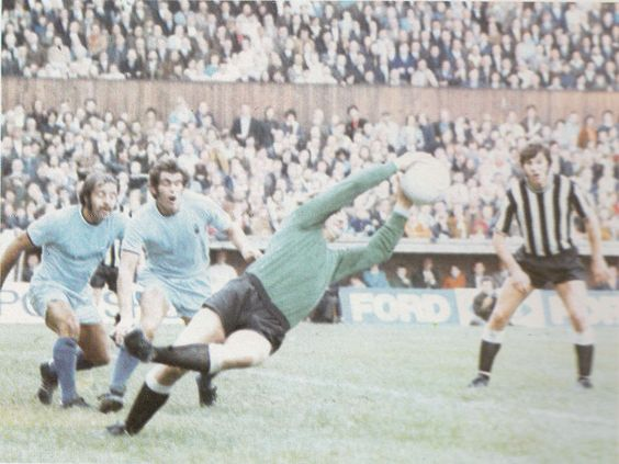 28th August 1971. Coventry City goalkeeper Bill Glazier makes desperate grab for the with team mates Jeff Blockley and Ernie Hunt rooted to the spot. Newcastle United centre forward Malcolm MacDonald ready to pounce.
