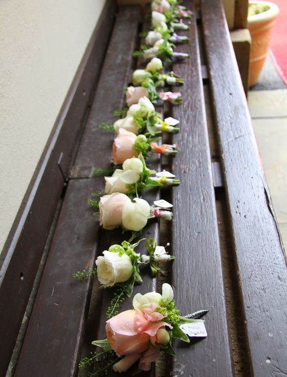 The individually created and multi coloured boutonnieres were all lined up ready to be pinned on to the special guests