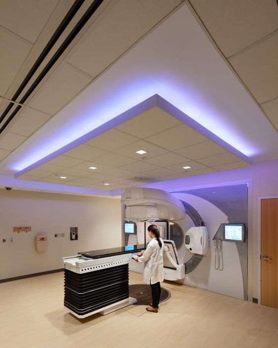 The cancer center houses two concrete linear accelerator vaults on the first floor, which support the radiation oncology program. Color-changing LEDs create a soothing environment for patients as they receive treatment. Light-colored, wood-look flooring contrasts with dark-colored, wood-look millwork to finish the interior. Decorative sliding acrylic panels conceal treatment accessories from patient view. Photo: ©Chris Cooper.