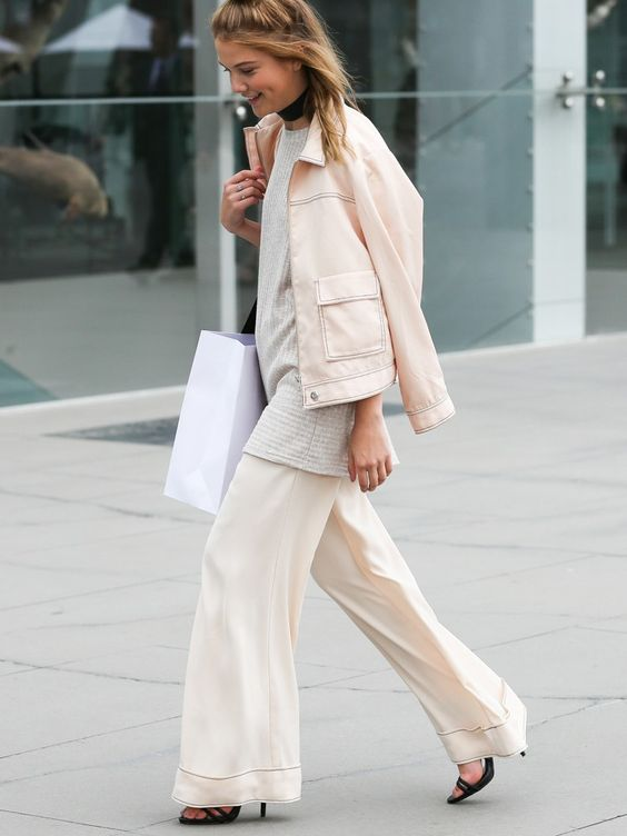 Cream wide leg trousers worn with coordinating jacket, a grey knit top underneath, a black neck choker and black sandal heels