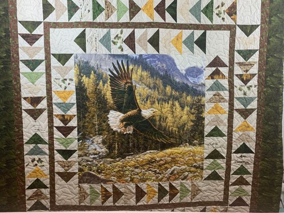 A great panel quilt with fantastic borders. Very masculine feel so we add a geometric design woth lots of angles to match all the triangles.