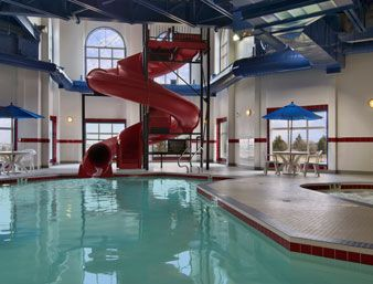Indoor pool and hot tub with a slide  Pool at the Ramada Sioux Falls Airport Hotel & Suites in Sioux ...