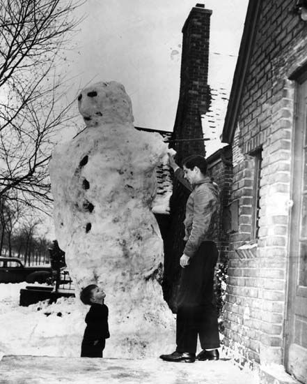 Raymond harbin rebuilds a huge snowman while bryce raynor 3 looks on