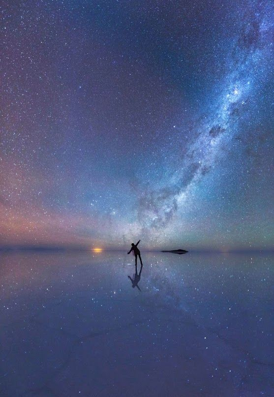The Mirrored Night Sky An enthralled stargazer is immersed in the stars as the luminous purple sky is mirrored in the thin sheet of water across the world's largest salt flat, Salar de Uyuni, in Bolivia. Credit: Xiaohua Zhao Insight Astronomy Photographer of the Year 2015 shortlist