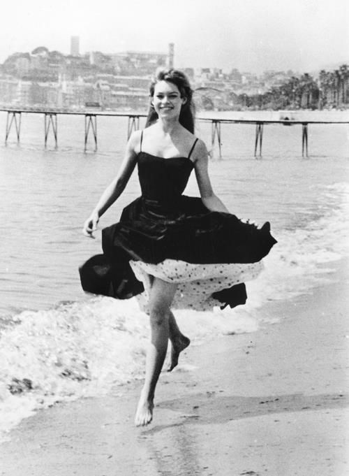 Brigitte Bardot strolling on the beach of Cannes during the Cannes Film Festival, on April 1956. © by Gamma