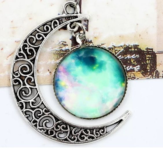 MOON AND GALAXY NECKLACE Silver tone necklace. Medallion is glass and alloy. About 20 inches long. Jewelry Necklaces