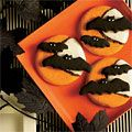 Dress up store-bought cocoa cookies with a spooky Halloween skyscape, courtesy of bat-shaped confections—with white sprinkles for eyes—and layers of tinted and plain vanilla frosting! #Halloween #party #recipe