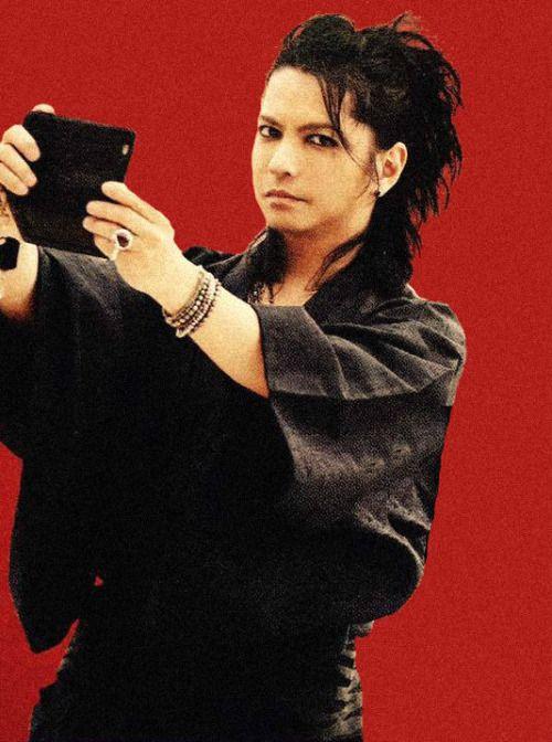 赤をバックにした黒い浴衣を着ているL'Arc〜en〜Ciel・hydeの画像