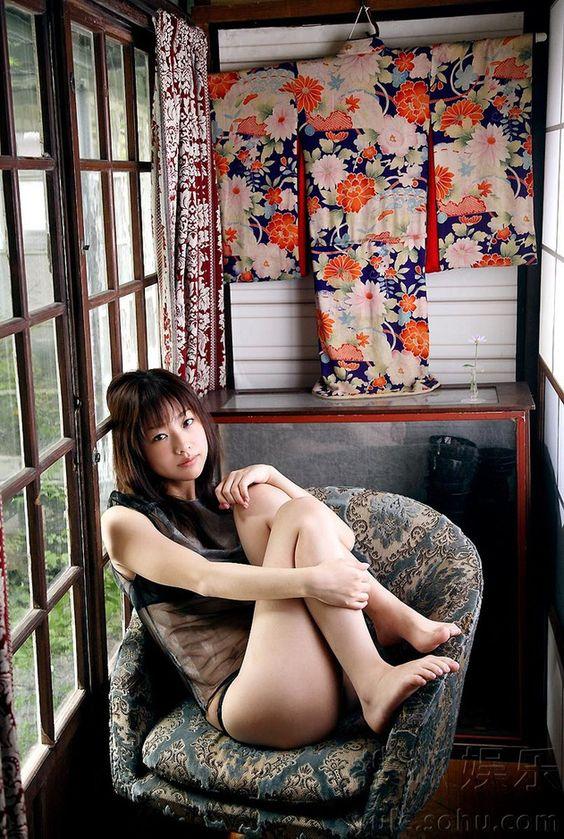 壁にかかった着物を背景に椅子に足を上げて座る椎名法子