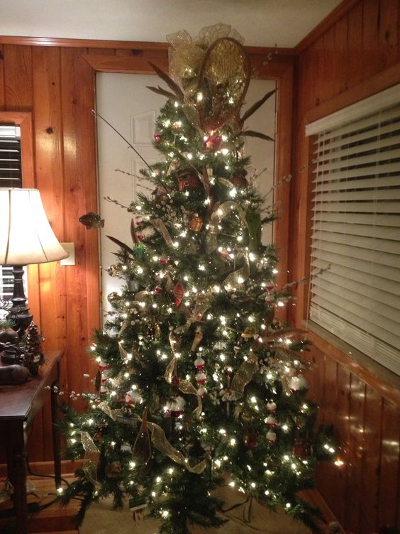 """Fishing and Fisherman themed christmas tree. I use pheasant feathers and pussy willow to dress it up a little. Great """"man"""" tree. I added the net and fishing rod from the garage to give it more character."""