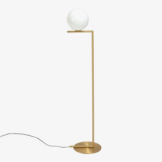 Form and function. Suspended from a brass rod, a blown glass orb emits soft…