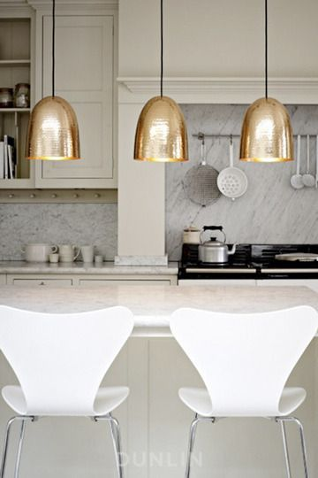 gold pendants against white and bone in this elegant kitchen...