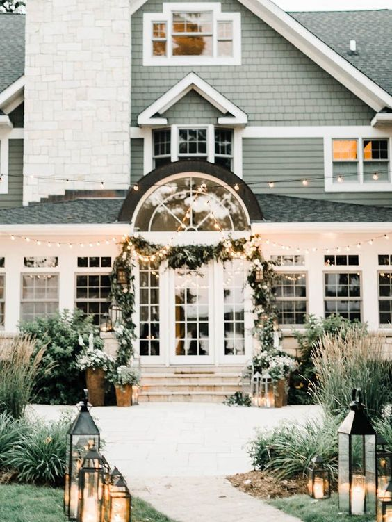 Green shingle style house decked out for Coastal Christmas with garland and lanterns