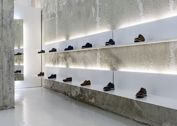 White Shelves Hang From Rough Concrete Walls At Shoe Shop