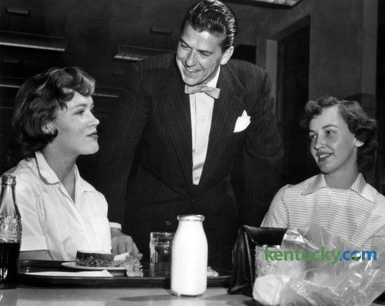 Screen and TV star Ronald Reagan met some of the employees  at the Lexington Lamp Works,  201 Rosemont Garden, during a tour of the plant  on Friday night, March 25, 1955. Here Reagan chats in the lunchroom of the  Lexington Lamp Works with Gretchen Boone (left), final inspector of  headlamps, and Bettye Watts, a tapper. A.D. Dixon was the plant manager at  the time. Reagan was the program supervisor of the General Electric Theater television series and came to Lexington  to visit two GE…