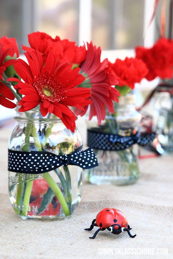 Idéia BBB: gérberas vermelhas colocadas em potes de vidro decorados com fitas de poás:
