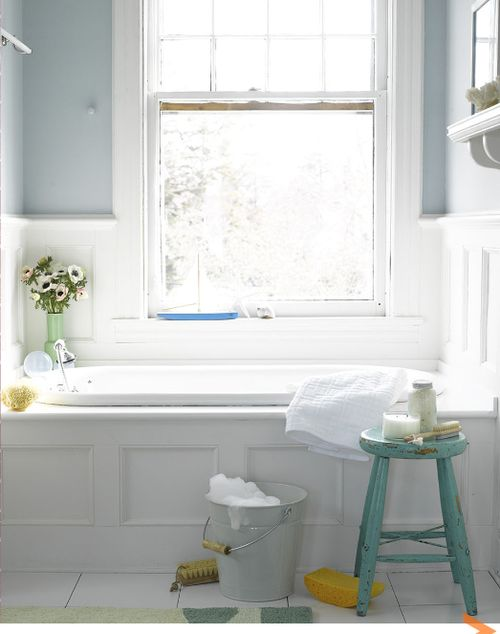 a large window over bathtub  flowers at one end of tub  white finishes with. a large window over bathtub  flowers at one end of tub  white