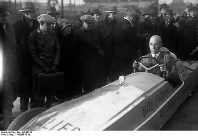 """Raketenauto der Adam Opel AG auf der Avus in Berlin, 23. Mai 1928  Das von der Adam Opel AG in Rüsselsheim entwickelte Raketenauto """"Rak 2"""", das von 24 Feststoffraketen angetrieben wird, erreicht auf der Berliner Avus, gesteuert von Max Valier (1895-1930), kurzfristig eine Geschwindigkeit von 230 km/h."""
