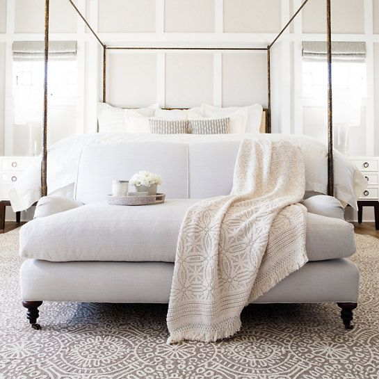 grey and whites in a pretty and soft pale bedroom with an iron bed and roll arm loveseat