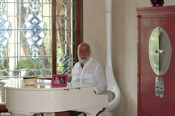 Gary sits at his white baby grand piano, which plays itself, as the light streams in throu...
