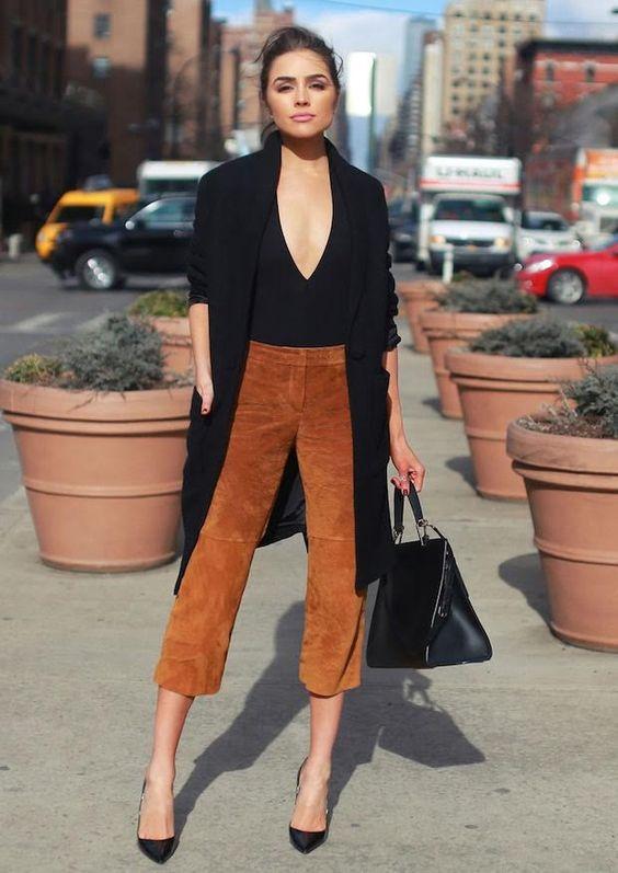 Confiira o estilo da fashionista americana Olivia Culpo, de calça culottes, ou pantacourt, suede, body decotado e sobretudo preto, completando com scarpin e bolsa da mesma cor.: