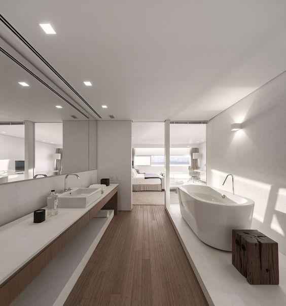 Banheiro da suite com banheira branca, piso de madeira, espelho em toda parede, armários de madeira e tampo branco. Cobertura Triplex no Rio de Janeiro  por Arthur Casas