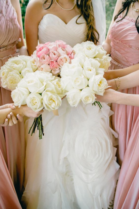 Bride's bouquet matches the color of bridesmaids dresses while bridesmaids hold white bouquets: