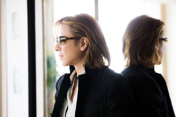 鏡を背にして立っているサングラスをかけたXJAPAN・YOSHIKIの画像