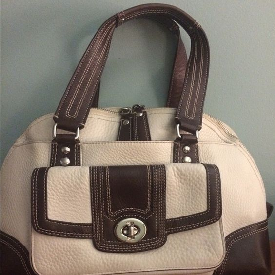 Coach satchel in cream leather w chocolate trim. Gorgeous Coach satchel in cream leather with chocolate trim.  Dust cover included.  Large exterior brass lock pocket with and addition oversize pocket behind.  Several useful interior pockets.  Minimal wear marks, which may be cleaned up easily.  Great for spring! Coach Bags Satchels