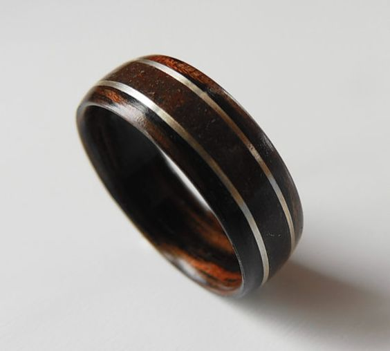 This bentwood ring is made of Macassar Ebony with a Dinosaur Bone and Silver inlay. The dinosaur bone was excavated in Utah. The Macassar