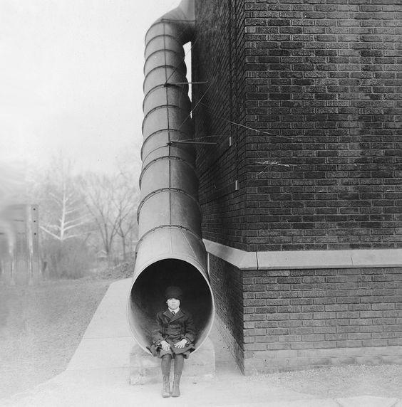 """Sentado en el extremo de una original salida de incendios """"Fire escape tube""""  :) en un edificio de ladrillo, 1924"""