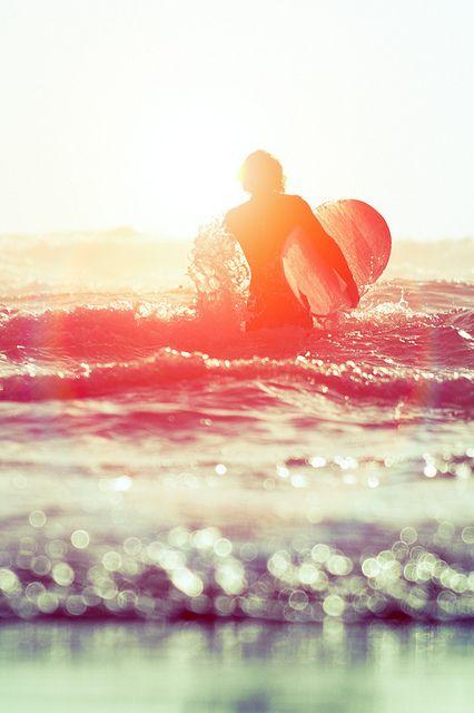 夕焼けとキラキラ光る水面とサーファー