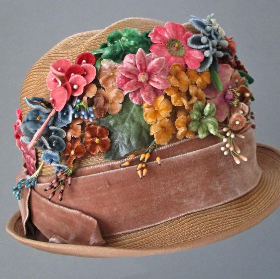 antique Flapper lady's cloche hat, c1920s. Warm honey-colored straw, covered with an abundance of colorful velvet flowers with delicate composition pistils and buds. Café-au-lait velvet ribbon band, gently rolled silk-covered brim.
