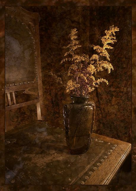 dark brown walls, antique chair and dried leaves in vase Brown and bronze