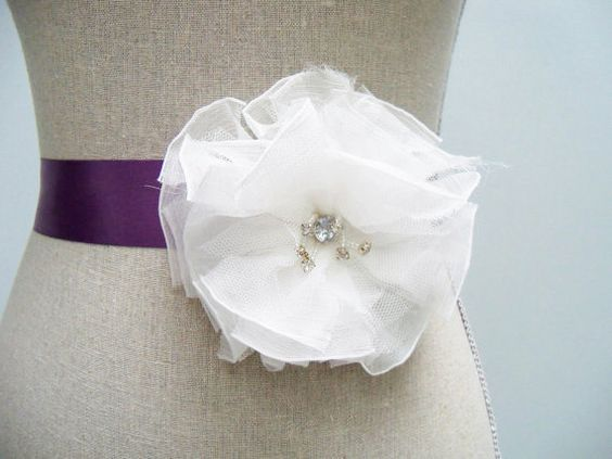 A beautiful purple sash with large flower to go with a wedding gown