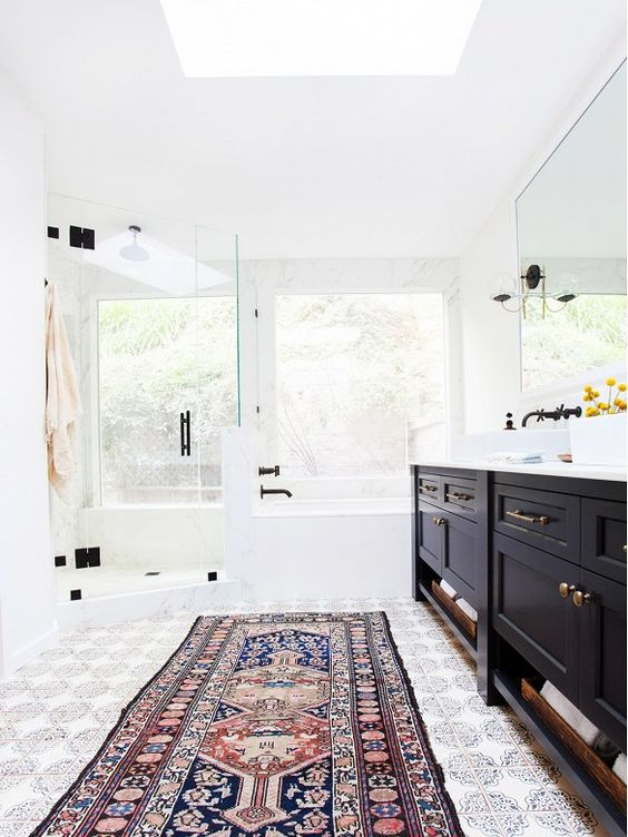 Bright master bathroom with glass shower, black cabinetry, and Persian runner.: