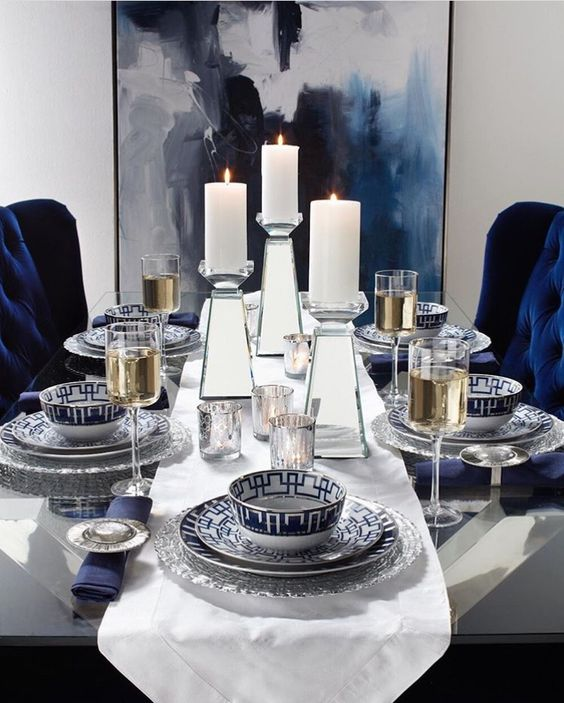 Bold and geometric #Navy and #Gold #DiningRoom #TableSetting with commanding #PillarCandle holders and elegant dish ware #HomeDecor #InteriorDesign